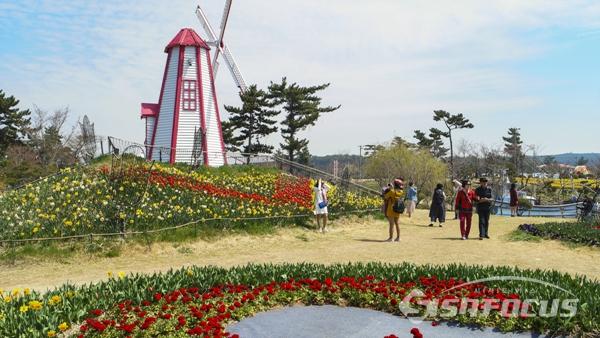 각종 조형물과 꽃를 조화롭게 조성한 꽃 축제장을 둘러보며 즐기는 관광객들 모습.  사진/강종민 기자